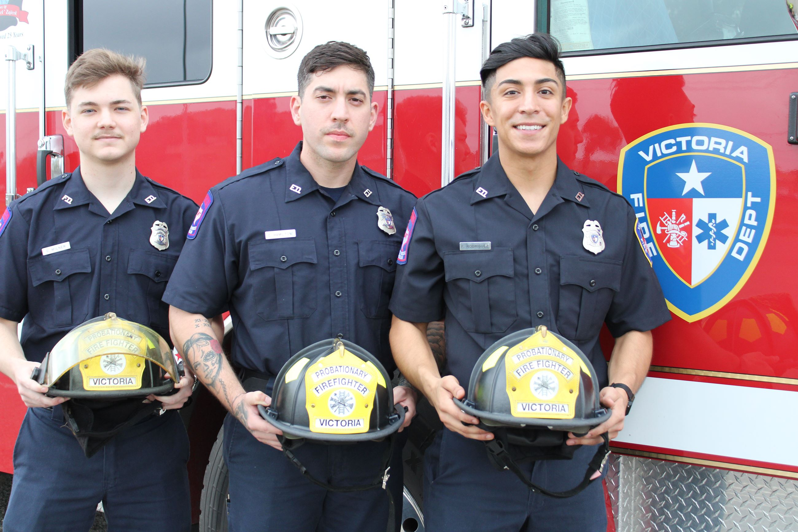 EMT firefighter trainees with helmets in front of fire truck