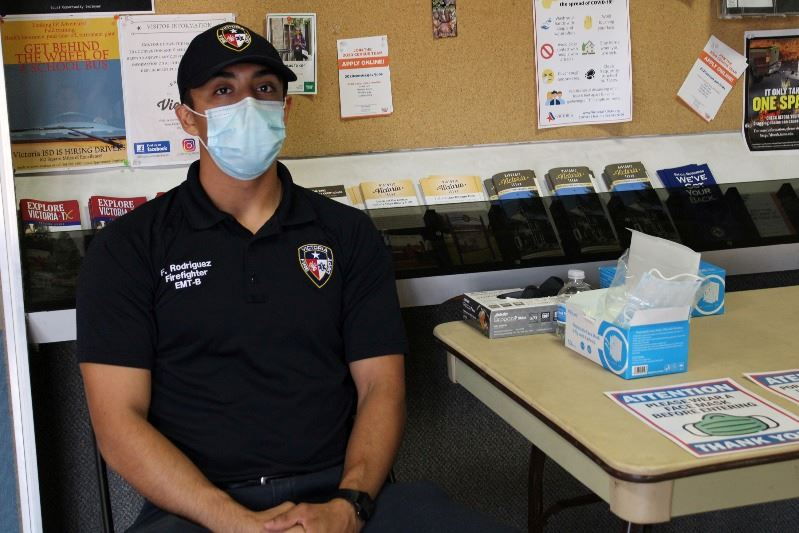 Firefighter EMT sits at table with box of masks