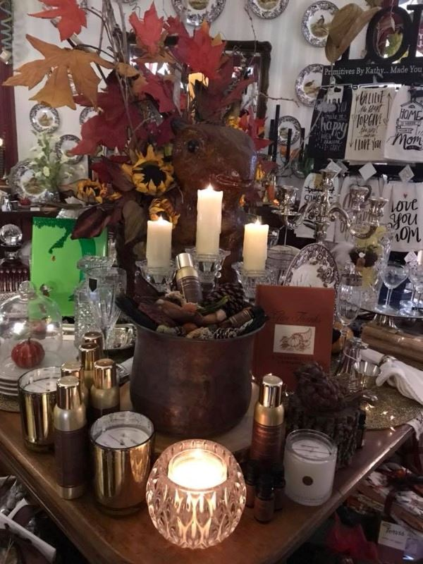 Picture of candles, gift items around a fall centerpiece.