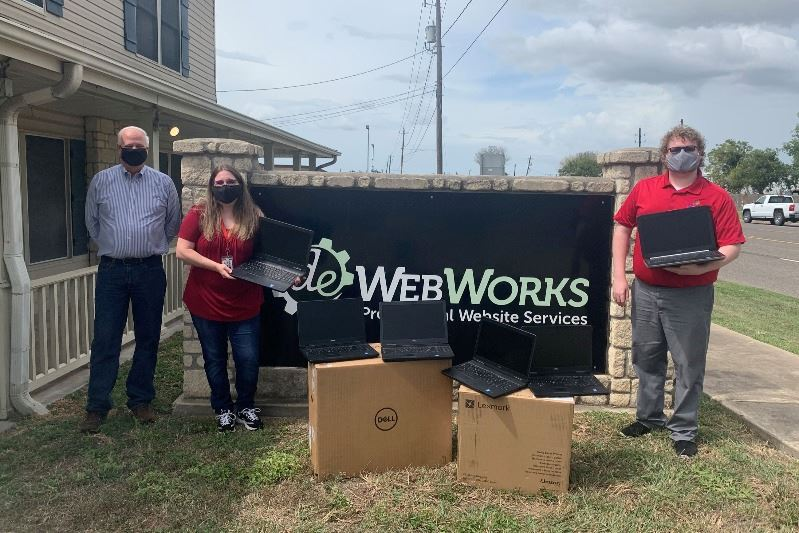 City staff, DE Webworks representative pose at DE Webworks sign with donated laptops