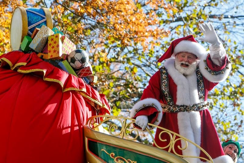 Santa Claus waves from sleigh-themed parade float. Trees are visible in the background.