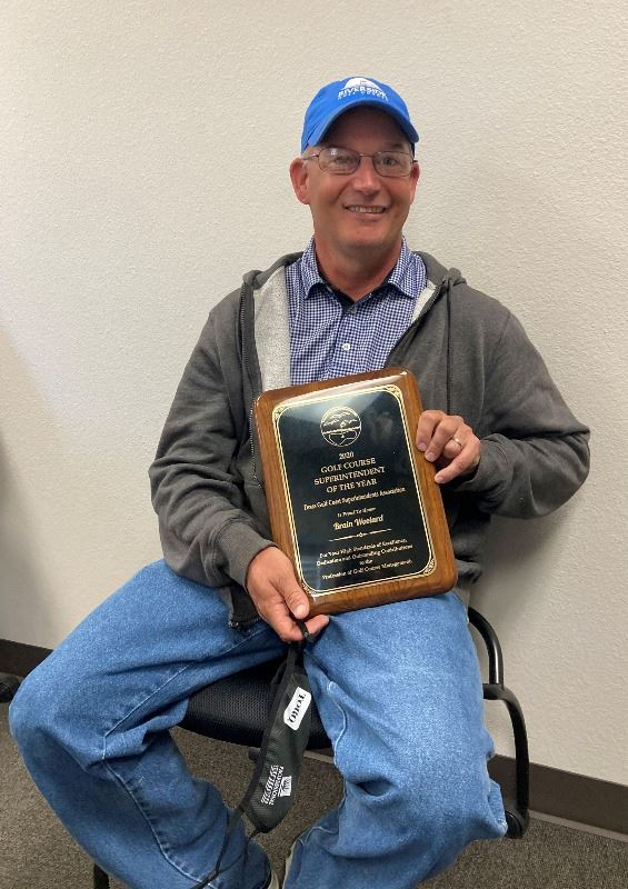 Riverside Golf Course Superintendent Brian Woolard, seated, poses with plaque