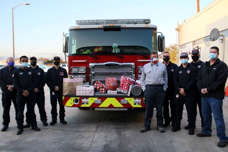 Firefighters stand in front of parked fire engine with wrapped gifts arranged across the front.