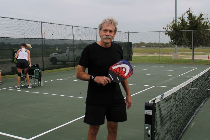 Man poses on a pickleball court with a pickleball racket