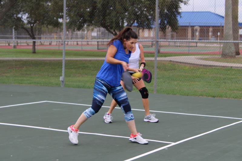 Woman playing pickleball hits the ball.