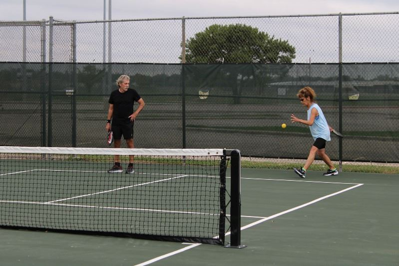 Man watches woman who is about to hit the ball during a game of pickleball.